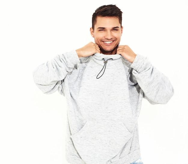 Il ritratto di giovane uomo di modello bello sorridente si è vestito in vestiti di maglia con cappuccio casuali grigi che posano sulla parete bianca. isolato