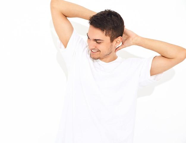 Il ritratto di giovane uomo di modello sorridente bello si è vestito nella posa dei vestiti e della maglietta dei jeans. toccandogli la testa