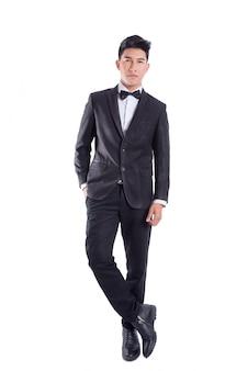 Il ritratto di giovane uomo sicuro asiatico si è vestito in smoking con il legame di arco isolato su priorità bassa bianca