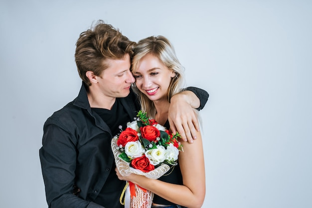 Il ritratto di giovani coppie felici ama insieme al fiore