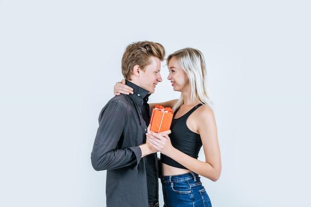 Il ritratto di giovani coppie felici ama insieme la sorpresa con il contenitore di regalo