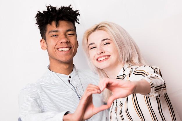 Il ritratto di giovani coppie interrazziali sorridenti che fanno il cuore modellano con le mani