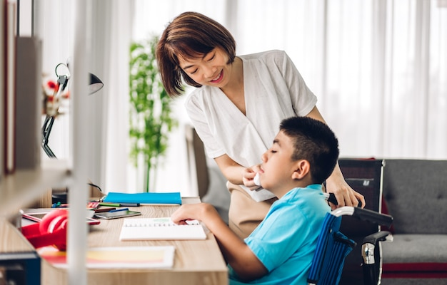 Il ritratto di gode della madre asiatica della famiglia felice di amore che gioca e che pulisce la bocca con il bambino disabile del figlio che si siede nei momenti della sedia a rotelle il buon tempo a casa
