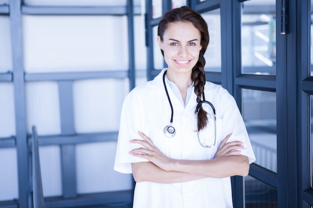 Il ritratto di medico femminile felice che sta con le armi ha attraversato in ospedale