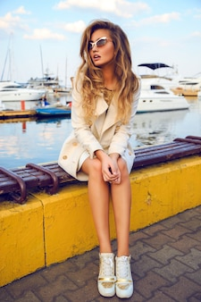 Il ritratto di moda all'aperto della bellissima modella, che indossa un vestito elegante e caldo con cappotto e scarpe da ginnastica, ha i capelli biondi arricciati alla moda, seduti allo yacht club della città. stile di strada autunnale.