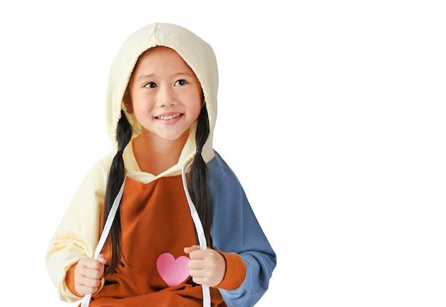 Il ritratto di piccola ragazza asiatica del bambino in cappuccio su vestiti caldi capi con tira la corda isolata su fondo bianco con lo spazio della copia.