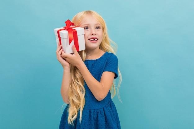 Il ritratto di piccola ragazza caucasica in vestito blu con capelli biondi lunghi tiene la scatola bianca con un regalo e sorrisi isolati su fondo blu