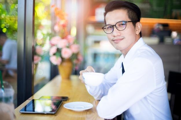 Il ritratto di riuscito uomo asiatico bello di affari beve il caffè con lo smartphone e la compressa