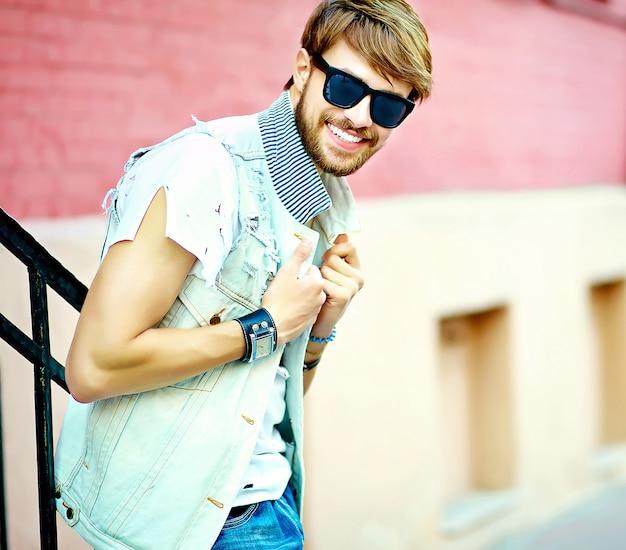 Il ritratto di stile di vita del tipo bello sorridente dell'uomo divertente dei pantaloni a vita bassa in estate alla moda copre la posa sul fondo della via in occhiali da sole