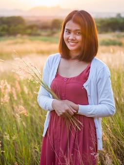 Il ritratto di stile di vita dell'estate di bella giovane donna che sorride e che tiene l'erba fiorisce con il tempo dell'alba o del tramonto.