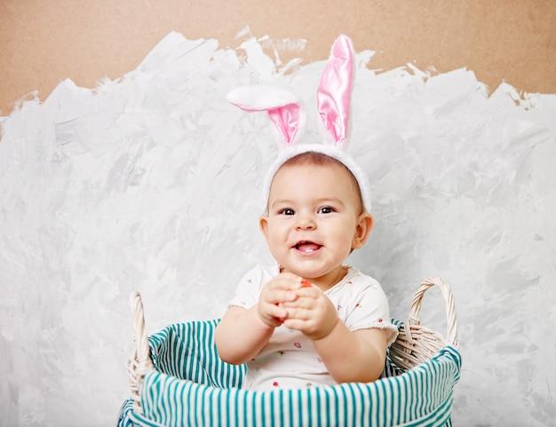 Il ritratto di un bambino sveglio vestito in orecchie del coniglietto di pasqua in un canestro tiene l'uovo