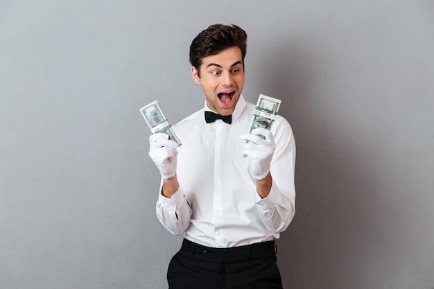 Il ritratto di un cameriere maschio emozionante felice si è vestito in unifrom