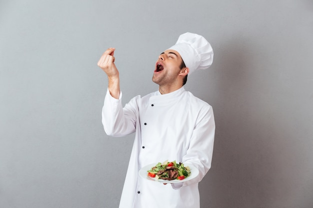 Il ritratto di un cuoco unico maschio felice si è vestito in uniforme