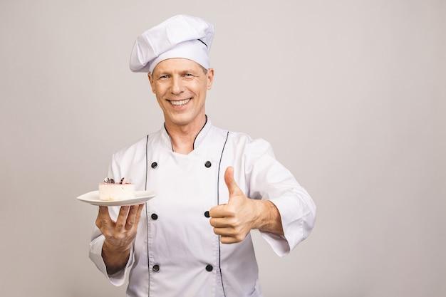 Il ritratto di un cuoco unico maschio senior felice si è vestito in piatto uniforme della tenuta con il pezzo di dolce pollici in su.