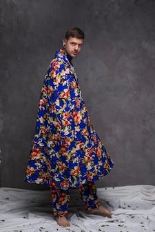 Il ritratto di un giovane dei pantaloni a vita bassa con floreale copre l'esame della macchina fotografica contro la parete grigia
