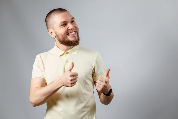 Il ritratto di un giovane in una maglietta gialla mostra come su gray.