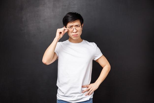 Il ritratto di un giovane studente maschio frustrato e sospettoso ha un lavoro part-time come tutor, sembra incredulo e confuso alla persona, fissa gli occhiali sugli occhi, socchiude gli occhi dubbioso, in piedi
