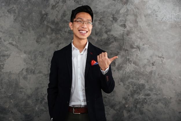 Il ritratto di un giovane uomo asiatico felice si è vestito in vestito