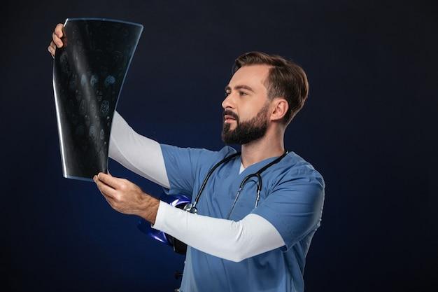 Il ritratto di un medico maschio concentrato si è vestito in uniforme