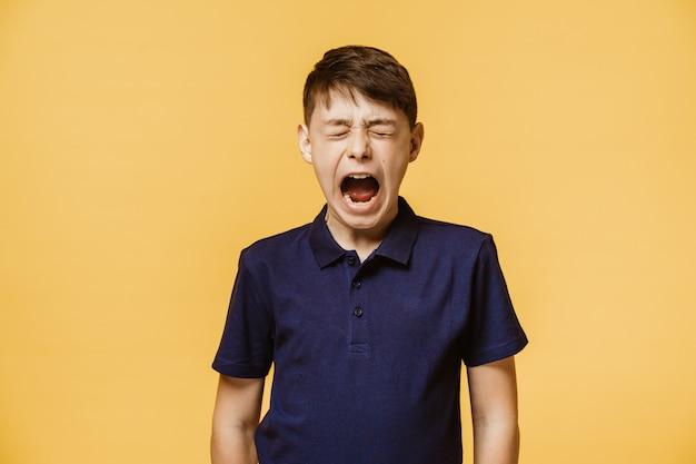 Il ritratto di un ragazzo che grida ad alta voce con gli occhi chiusi, indossa una maglietta viola scuro, isolata sopra la parete gialla