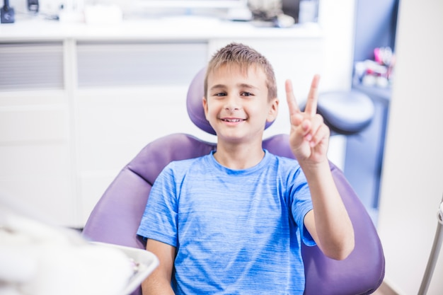 Il ritratto di un ragazzo felice che gesturing la vittoria firma dentro la clinica