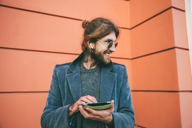 Il ritratto di un uomo barbuto sorridente si è vestito in cappotto