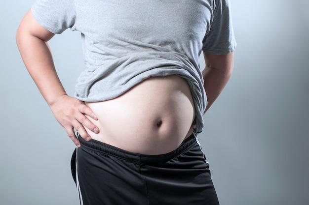 Il ritratto di un uomo grasso asiatico mostra il suo corpo e la grande pancia.