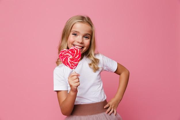 Il ritratto di una bambina felice che tiene il cuore ha modellato la lecca-lecca