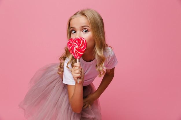 Il ritratto di una bambina graziosa che tiene il cuore ha modellato la lecca-lecca