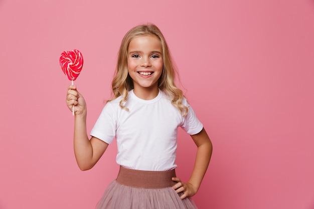 Il ritratto di una bambina sorridente che tiene il cuore ha modellato la lecca-lecca