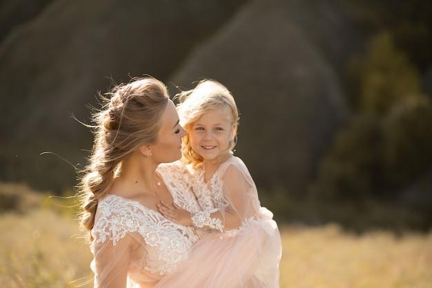 Il ritratto di una bella giovane mamma tiene la sua amata figlia tra le braccia. amore dei genitori, piccola principessa