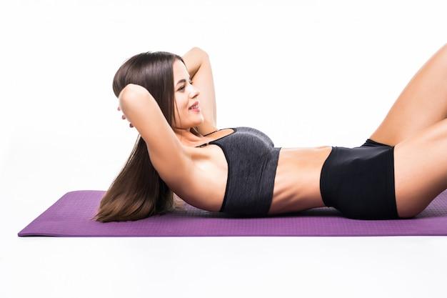 Il ritratto di una donna di forma fisica che fa l'abs si esercita isolato su un bianco