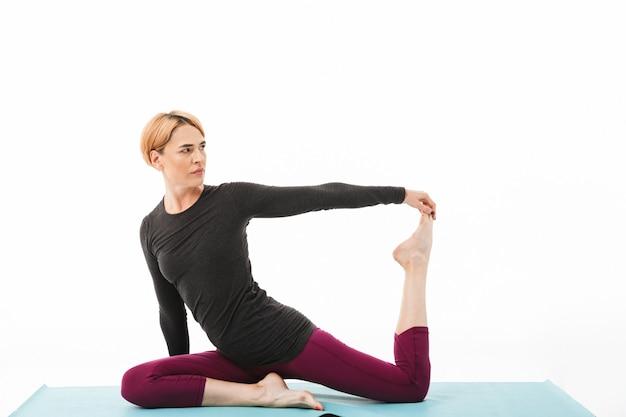 Il ritratto di una donna in buona salute di yoga si è vestito in vestiti di sport