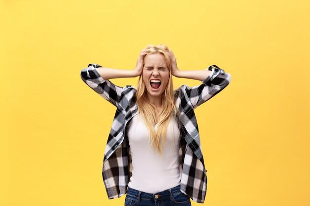 Il ritratto di una donna irritata arrabbiata con le mani ha sollevato gridare alla macchina fotografica isolata su fondo giallo