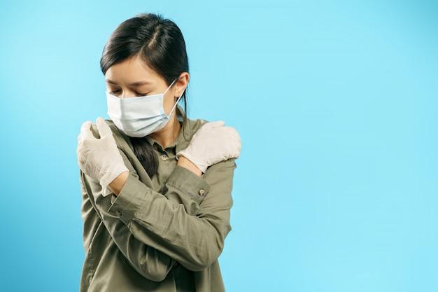 Il ritratto di una donna turbata in una mascherina chirurgica e guanti protettivi con le braccia ha attraversato su una priorità bassa blu. paura e orrore durante una pandemia.
