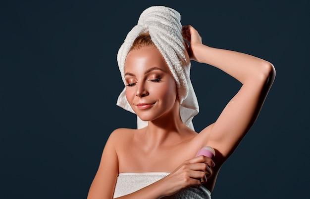 Il ritratto di una giovane donna attraente con un asciugamano in testa usa una palla antitraspirante su un muro nero.