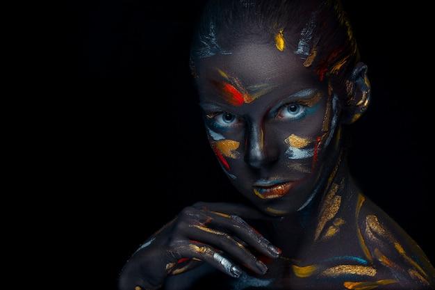 Il ritratto di una giovane donna che sta posando è coperto di pittura nera