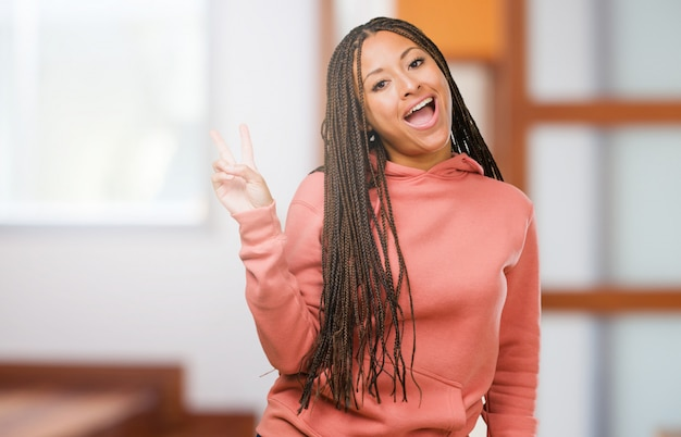 Il ritratto di una giovane donna di colore che indossa le trecce divertimento e felice