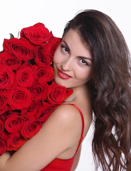 Il ritratto di una giovane donna graziosa si è vestito in mazzo rosso della tenuta del vestito delle rose isolate sopra fondo bianco