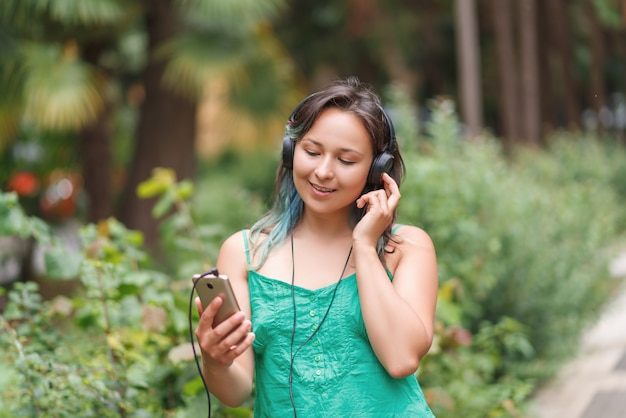 Il ritratto di una giovane donna intelligente in estate copre l'ascolto della musica con le cuffie mentre tiene il telefono cellulare sull'erba attraverso le palme. concetto di libertà.