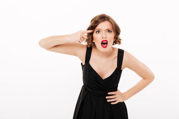 Il ritratto di una ragazza arrabbiata si è vestito in vestito nero