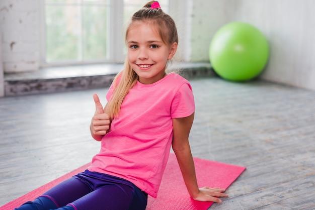 Il ritratto di una ragazza che si siede sull'esercitazione della stuoia che mostra i pollici aumenta il segno