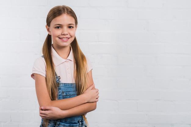 Il ritratto di una ragazza felice con il braccio ha attraversato lo sguardo alla macchina fotografica che sta contro la parete bianca