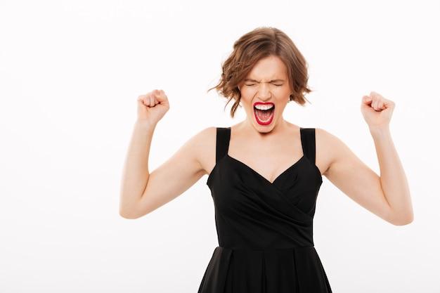 Il ritratto di una ragazza furiosa si è vestito in vestito nero che grida