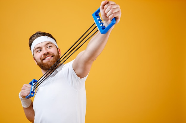 Il ritratto di uno sportivo allegro che fa la forma fisica si esercita con l'espansore