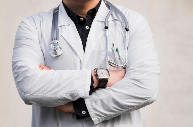 Il ritratto di uno stetoscopio maschio della tenuta di medico intorno al suo collo che sta con le armi ha attraversato contro il contesto bianco