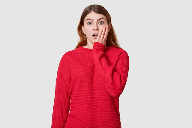 Il ritratto emotivo di bella ragazza alla moda ha vestito il maglione rosso che posa sopra il bianco