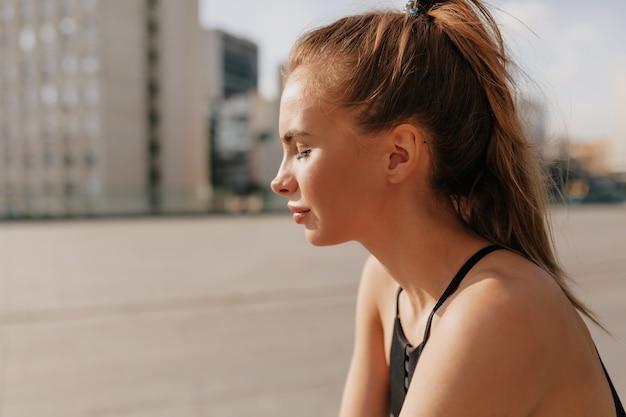 Il ritratto esterno di giovane persona attraente in uniforme sportiva ha una pausa tra gli esercizi. donna di sport facendo esercizi alla luce del sole