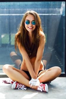 Il ritratto estivo di moda luminosa per interni di donna elegante hipster felice, fuma e si diverte, ha capelli lunghi castani abbronzati perfetti corpo snello, indossa un top corto e occhiali da sole rotondi.