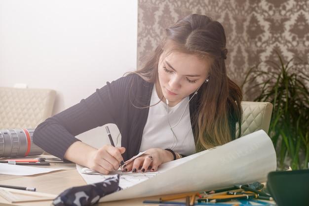 Il ritratto frontale di una giovane studentessa è impegnato al tavolo disegna schizzi, schizzi, piani, architettura. formazione e pratica